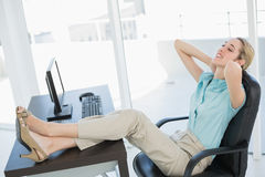 Classy young businesswoman relaxing sitting on her swivel chair Stock Photos