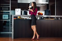 Classy young Latin woman drinking coffee standing in the kitchen relaxing after shopping.  royalty free stock image