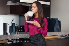 Classy young Latin woman drinking coffee standing in the kitchen relaxing after shopping.  stock photography