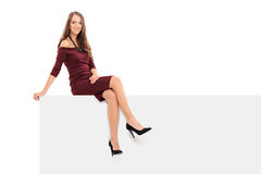 Classy young woman sitting on a blank panel Royalty Free Stock Photography