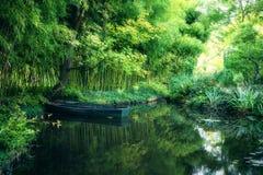 Claude Monet i höstträdgården, fartyg i sjön bland bambudungarna arkivbild