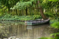 Claude Monet in summer garden. Boat in the lake among the bamboo groves Stock Photo