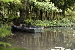 Claude Monet in summer garden. Boat in the lake among the bamboo groves Stock Photography