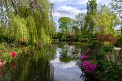 The water garden of Claude Monet in spring. Claude Monet water garden, which served as a model for the series of water lilies, is inspired by Japanese gardens Stock Images