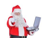 claus holdingbärbar dator som pekar santa Arkivbild
