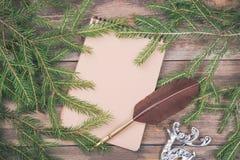 claus meddelande santa till Filialer för julgranträd på träbräde med den tomma anteckningsbok- och vingpennafjäderpennan Jul elle Royaltyfria Bilder