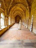 Claustro interno de uma abadia com uma monge que anda e que reza imagens de stock royalty free