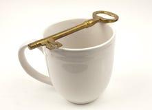 Clave de oro sobre una taza blanca imagen de archivo libre de regalías