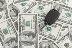 Clave del coche en fondo de 100 dólares Fotografía de archivo