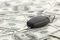 Clave del coche en fondo de 100 dólares Imagen de archivo libre de regalías