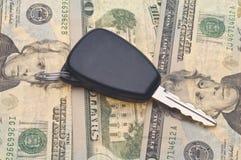 Clave del coche en fondo del dinero Foto de archivo libre de regalías