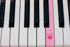 Clave del piano con el icono del corazón Imagenes de archivo