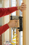 Clave el arma que es utilizado para instalar el ajuste de madera alrededor de los wi Imágenes de archivo libres de regalías