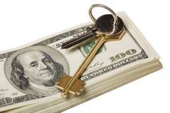 Clave y dinero en el fondo blanco Fotos de archivo
