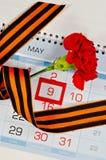 Clavel rojo brillante envuelto con la cinta de George que miente en el calendario con la fecha enmarcada del 9 de mayo Foto de archivo libre de regalías