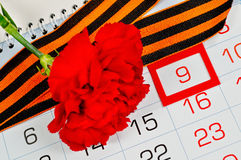 Clavel rojo brillante envuelto con la cinta de George que miente en el calendario con la fecha enmarcada del 9 de mayo - tarjeta  Fotos de archivo libres de regalías