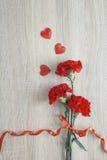 Claveles rojos con la cinta y corazones en un fondo de madera Foto de archivo