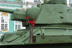 Claveles rojos en el T-34 Foto de archivo libre de regalías