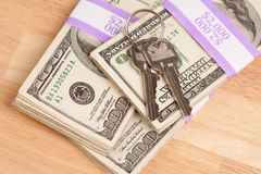 Claves de la casa en la pila de dinero Imagen de archivo libre de regalías