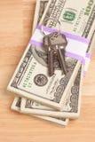 Claves de la casa en la pila de dinero Imagenes de archivo