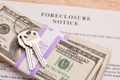 Claves de la casa, pila de dinero y aviso de la ejecución de una hipoteca Fotos de archivo