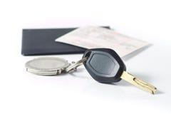Claves del coche con el documento del seguro detrás sobre blanco Foto de archivo libre de regalías