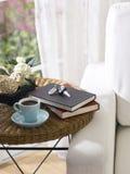 Claves del coche, taza de té y libros Fotografía de archivo libre de regalías