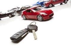 Claves del coche y varios coches de deportes en blanco Imagen de archivo