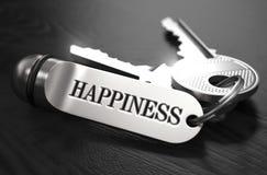 Claves a la felicidad Concepto en llavero de oro Foto de archivo