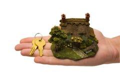 Claves y casa en la mano Foto de archivo