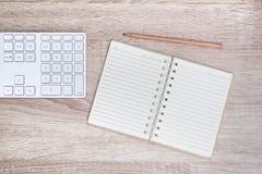Clavier, bloc-notes, crayon, et équipement de bureau modernes sur le bureau en bois Photographie stock libre de droits