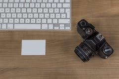 Clavier d'appareil-photo et carte de visite professionnelle de visite sur un bureau Images stock