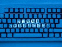Clavier d'ordinateur avec le Joyeux Noël des textes sur des boutons couverts de neige illuminée par la lampe au néon bleue Photo libre de droits