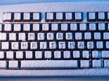 Clavier d'ordinateur avec le Joyeux Noël des textes sur des boutons couverts de neige illuminée par la lumière latérale Image stock