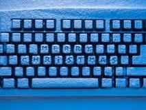 Clavier d'ordinateur couvert de neige illuminée par la lampe au néon bleue avec le Joyeux Noël d'inscription Images stock