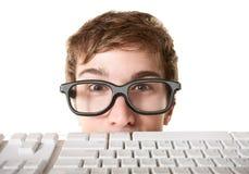 Clavier d'ordinateur derrière de l'adolescence Images stock