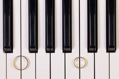 Clavier de piano et anneaux de mariage Images stock