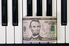 Clavier de piano et billet de banque de dollar US Photos libres de droits