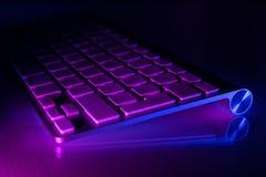 Clavier en aluminium illuminé dans refléter bleu et pourpre sur le gl photographie stock