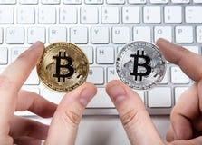 Clavier et deux pièces de monnaie de bitcoin dans la main d'un homme Photo stock