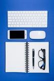 Clavier, lunettes, smartphone et carnet sur la table de bureau Photographie stock