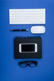 Clavier, lunettes, smartphone et carnet sur la table de bureau Photo libre de droits
