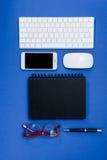 Clavier, lunettes, smartphone et carnet sur la table de bureau Images libres de droits