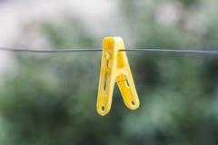 Clavija de ropa amarilla colorida en filamento Imagen de archivo
