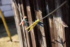 Clavijas de ropa amarillas y azules en cuerda para tender la ropa fotos de archivo libres de regalías