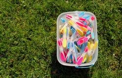 Clavijas de ropa brillantemente coloreadas en un cubo en hierba verde en sol Imagen de archivo libre de regalías