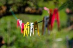 Clavijas de ropa coloridas en línea fotos de archivo libres de regalías