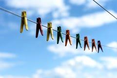 Clavijas de ropa plásticas brillantes clasificadas en una línea que se lava Foto de archivo