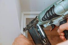 Clavito del carpintero usando el arma del clavo al ajuste que enmarca que moldea, con la etiqueta de advertencia herramientas elé Fotos de archivo libres de regalías