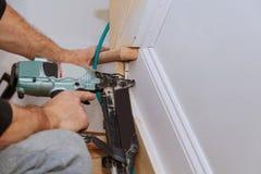 Clavito del carpintero usando el arma del clavo al ajuste que moldea, con la etiqueta de advertencia herramientas eléctricas ese  Foto de archivo libre de regalías